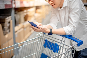 Young Asian man standing with cart checking the shopping list in warehouse wholesale, shopping warehousing concept