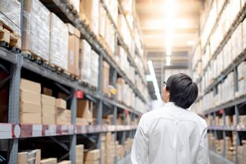 Young Asian man standing between cardboard box shelves in warehouse choosing what to buy, shopping warehousing concept