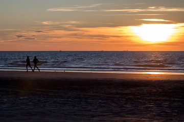Couple silhouette running during sunset at the beach