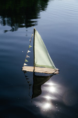 A diy boat from driftwood is floating in a dark lake with sunlight reflecting in the water.