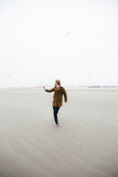 A man in a brown coat running on a beach flying a kite on a grey and misty day.