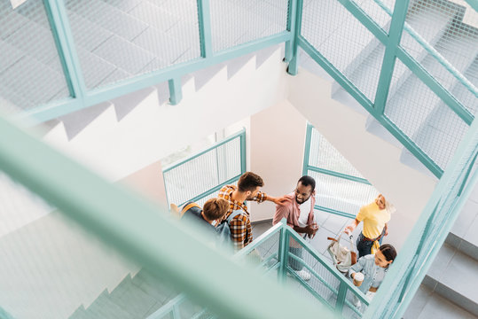 high angle view of young students walking down stairs at college