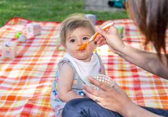 Mother feeding baby with spoon 1