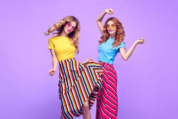 Wall Mural - Two Girls Jumping Having Fun.Fashion Summer Outfit