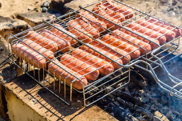 Sausages cooking in a barbecue grill on campfire