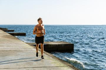 sporty adult shirtless man jogging on seashore
