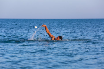 Young man swimming front crawl in sea