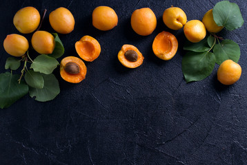 Delicious ripe apricots  on black background, close-up. Fruit banner. Selection of healthy vegetarian food, detox or diet concept, space for text. View from above, top studio shot