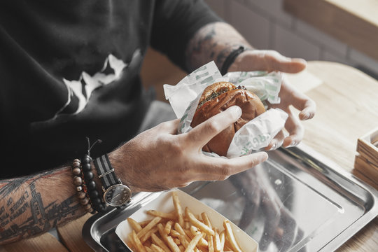 Young tattooed man eating burger at cafe.