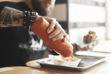 Young bearded man pours ketchup on french fries close up.