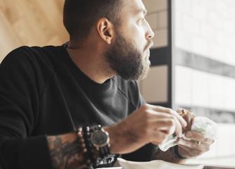 Young bearded man eating burger close up.