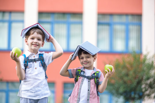 Child going to school. Boy and his friend holding books on head like house roof on the first school day.