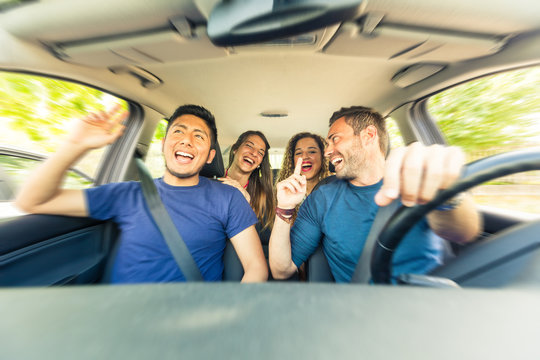Friends inside the car singing during a road trip