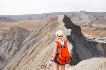 A girl in a straw hat and with a backpack walks along a mountain ridge in the middle of the desert.