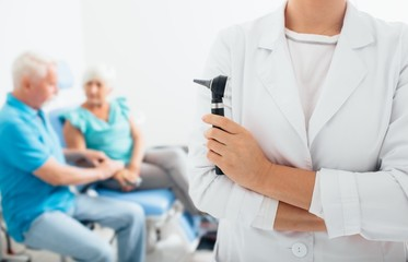smiling doctor standing before elderly patients in medical office