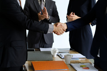 Business handshake at meeting or negotiation in the office, close-up. Partners are satisfied because signing contract