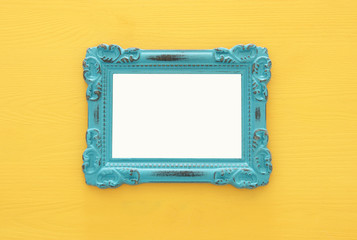 Vintage blank blue photo frame over yellow background. Ready for photography montage. Top view from above.