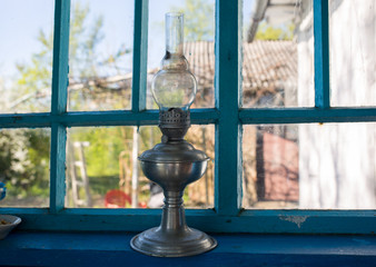 Old vintage gas lamp standing in the house on blue scratched window sill. Rustic natural photo.