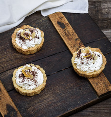 sweet cakes with white cream on a brown wooden board