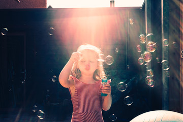 little girl plays with soap bubbles