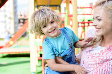 selective focus of smiling mother embracing and holding little son at playground