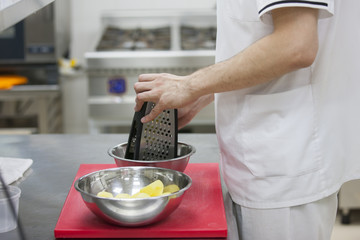 Chef grinds potatoes Chef's hands, chopping board, grater Close-up