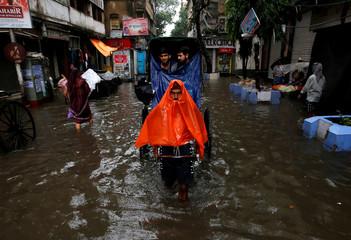 A rickshaw puller transports passengers through a water-logged street after heavy rain in Kolkata