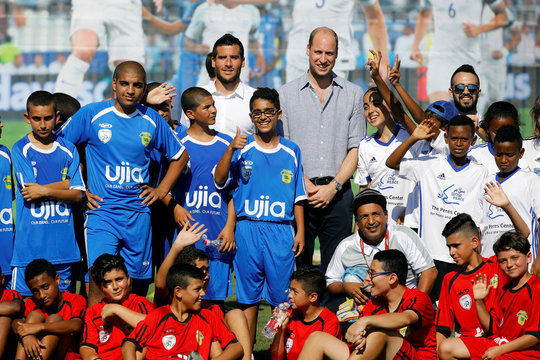 Britain's Prince William and Tomer Hemed, an Israeli professional footballer, pose for a photo with Jewish, Muslim and Christian children during a soccer event organized by The Equalizer and Peres Center for Peace in Jaffa