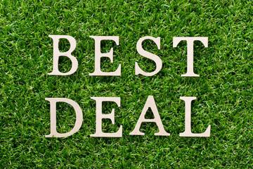 Wood alphabet in word best deal on artificial green grass background
