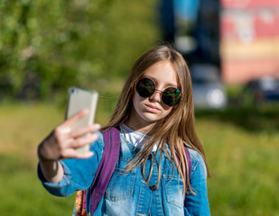 Little girl schoolgirl. Summer in nature. In his hands holds a smartphone. In sunglasses and a denim jacket. He takes pictures of himself on a smartphone. Make a video call over the Internet.