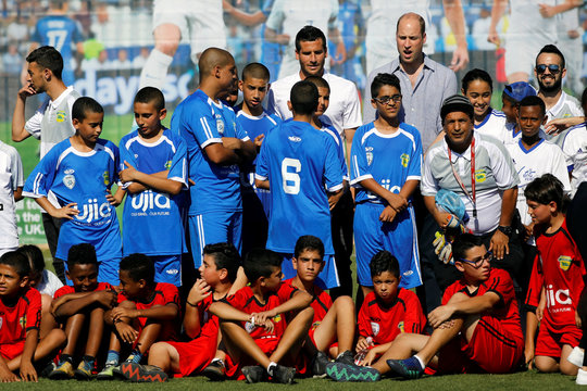 Britain's Prince William and Tomer Hemed pose for a photo with Jewish, Muslim and Christian children during a soccer event organized by The Equalizer and Peres Center for Peace in Jaffa