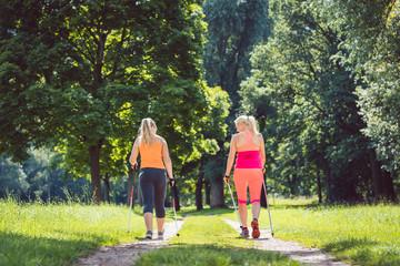 Mutter und Tochter beim Nordic Walking für bessere Fitness