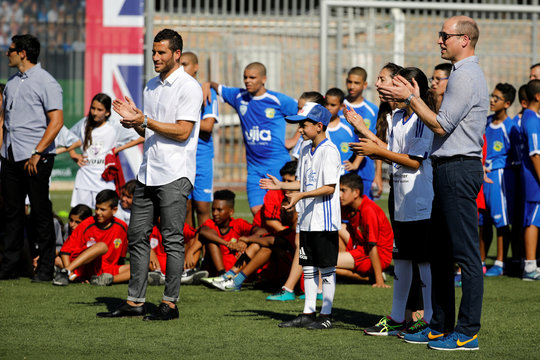 Britain's Prince William applauds as he stands with Tomer Hemed during a soccer event with Jewish, Muslim and Christian children organized by The Equalizer and Peres Center for Peace in Jaffa