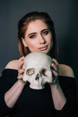A beautiful girl in black clothes with a skull in her hands. Gothic fashion. A model on a gray background. Studio portrait