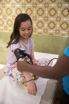 Little multicultural girl on a doctor well-visit, getting blood pressure measured