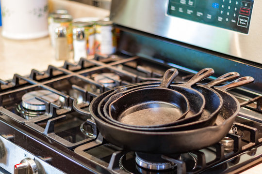 Iron skillets stacked on top of a stove top in a kitchen.