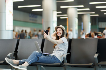 Young smiling traveler tourist woman working on laptop, doing selfie on mobile phone waiting in lobby hall at international airport. Passenger traveling abroad on weekends getaway. Air flight concept.