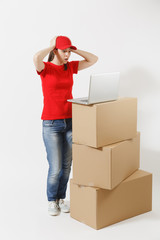 Full length portrait of delivery young woman in red cap, t-shirt isolated on white background. Female courier standing near empty cardboard boxes with laptop pc computer. Receiving package. Copy space