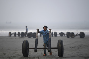 A Rohingya refugee child pushes fishing boat wheels on Shamlapur beach in Cox's Bazaar