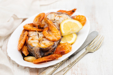 boiled fish with shrimps and lemon on white dish