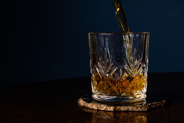Whiskey being poured into a crystal tumbler from an angle on a dark wooden table