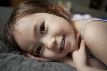 Close shot of pre-school 4 year-old girl smiling sweetly to camera