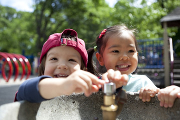 Two kids at the water fountain in city park in summer
