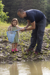 Girl catching frogs with her father in the country