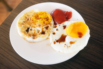 Two fried eggs with tomato sauce and soy sauce in white plate on wooden table for breakfast..