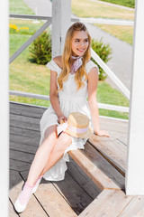 high angle view of beautiful smiling girl in white dress sitting on wooden bench and looking away