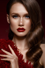 A beautiful girl with evening make-up, a Hollywood wave and red lips. Beauty face. Photo taken in the studio.