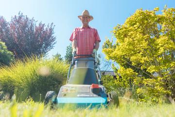 Senior Mann beim Rasenmähen in seinem Garten