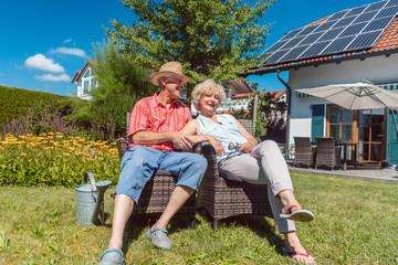 Senior Paar sitzt im Garten vor seinem Haus
