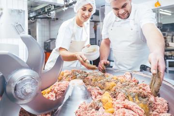 Fleischer würzen das Hackfleisch als Wurst Rohmasse